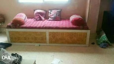 brown and white wooden bed frame with red mattress