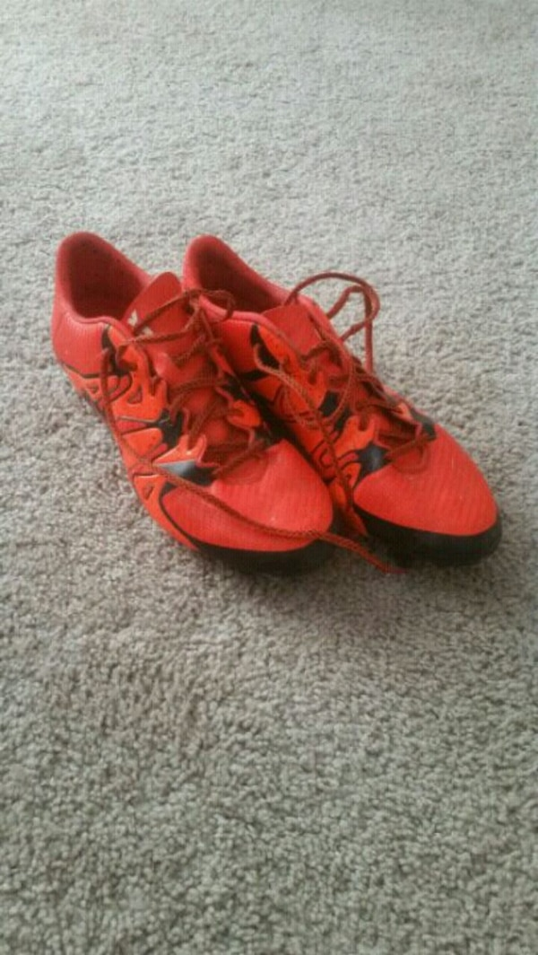 pair of red Adidas cleats