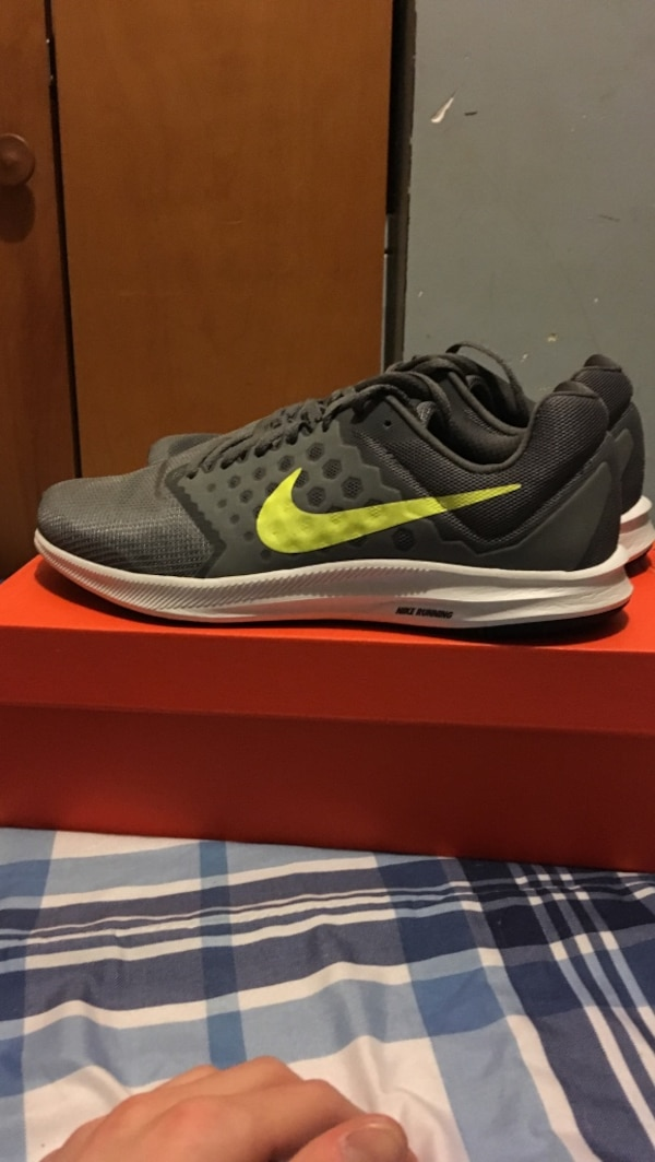 pair of gray Nike running shoes on box