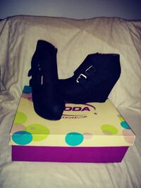 pair of black wedge shoes with purple box