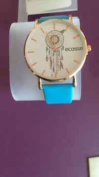 round gold analog watch with blue leather strap