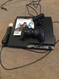 Black sony ps3 console with controller and game cases