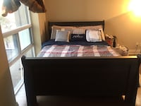 black wooden bed frame with red-white-and-gray plaid comforter set