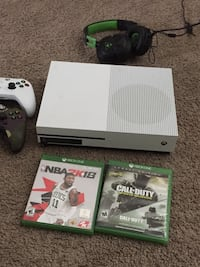 White xbox one console with controller and game cases