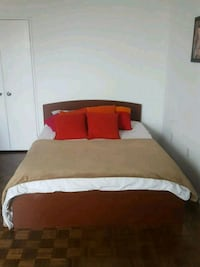 brown wooden bed frame with white bed sheet