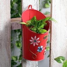 red and pink floral metal planter pot with green leaf plant