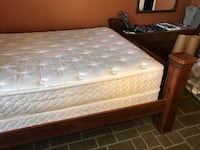 Brown wooden bed frame with white mattress Saskatoon