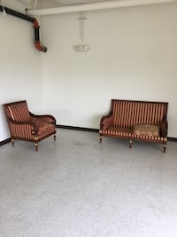Two brown wooden framed brown padded armchairs Frederick