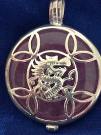 Good Luck Sterling Silver Jade Dragon Pendant  Sterling silver dragon pendant features a charming dragon resting on a disc of purple Jade. The creature embodies some of the unique myths that have surrounded dragons for many years. These mythical creatures