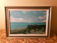 painting of cars parked near seashore with gray wooden frame
