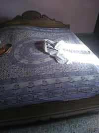 purple and white floral quilt; brown wooden bed frame New Delhi, 110028