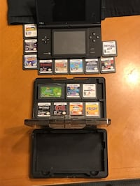 Black nintendo ds with game cartridges
