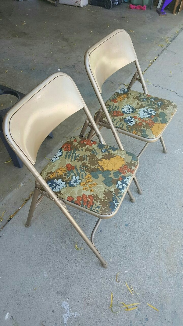 two white floral folding chairs