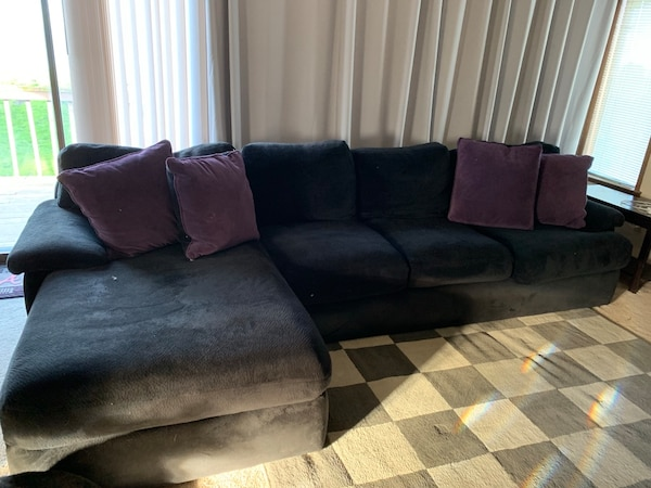 black suede sectional sofa with throw pillows
