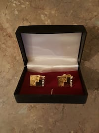 pair of gold-colored cuffling with box