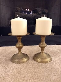 Two brass-colored pillar candle holders