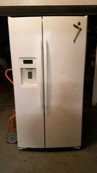 GE Refrigerator side by side with ice and water dispenser.