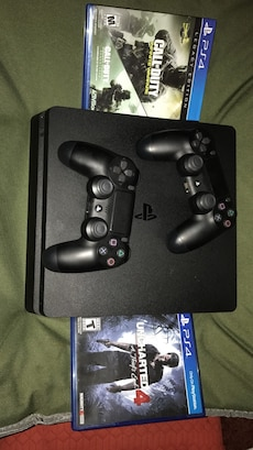 black Sony PS4 game console with game cases