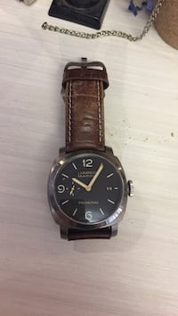 round black analog watch with brown leather strap