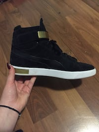 Black high-tops pumas with gold straps
