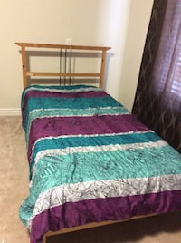 brown wooden bed frame with blue and purple comforter set Calgary