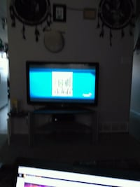 black flat screen TV with brown wooden TV stand Edmonton, T5W 5J7