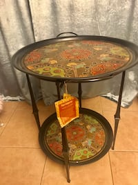 New tray made in India. Hand painted tray that is forged from iron. Top tray is removable and can be used as a serving tray. Excellent condition . Jacksonville Beach