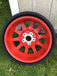 Red multi-spoke car wheel with tire