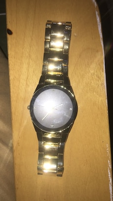 round gray analog watch with gold strap