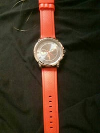 round silver chronograph watch with orange leather