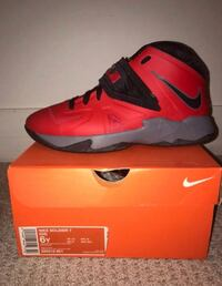 Unpaired red and black nike basketball shoe on box