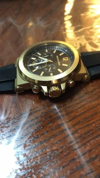 Round gold-colored chronograph watch with black strap 874 km