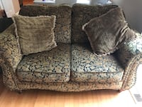 Brown and black floral loveseat and sofa with throw pillows