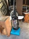 blue and black Bissell upright vacuum cleaner