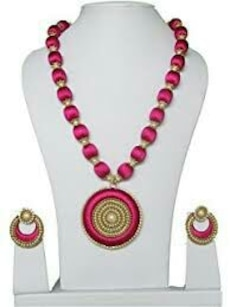 pair of pink dangling earrings and medallion pendant necklace