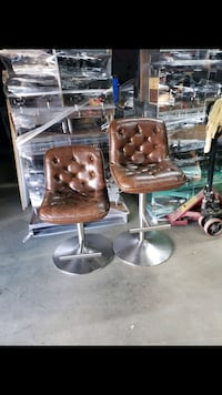 Two brown adjustable barstools