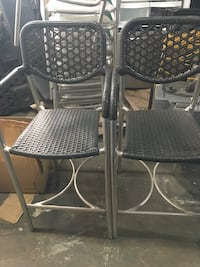two gray metal framed padded chairs
