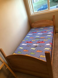 multicolored bed sheet and brown wooden bed frame Calgary, T2K 5E1