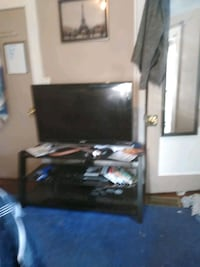 flat screen TV and brown wooden TV hutch 303 mi