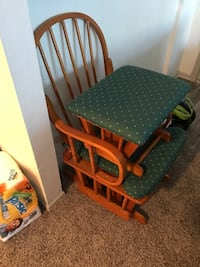 Brown wooden framed green padded rocking chair