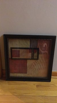 Brown wooden framed painting of brown wooden house.