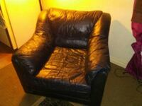 black leather sofa chair with throw pillow