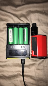 Red and black variable box mod with four green 18650 batteries and black charger