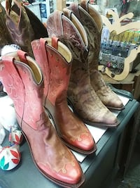 two pairs of red and brown leather cowboy boots