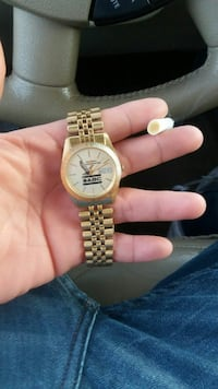 round gold-colored analog watch with chain bracelet