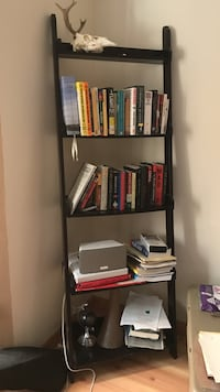 Black wooden 5-layered shelf-very sturdy and has a couple scratches on the edges towards the bottom.