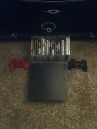 black Sony PS3 console with controller and game ca