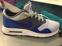 unpaired white, black, and blue Nike low top shoe