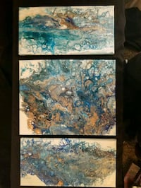 three blue-and-brown paint splattered abstract paintings