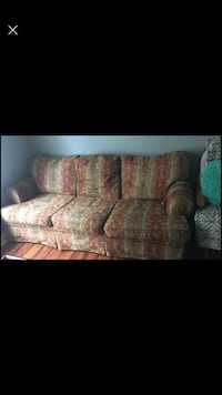 couch and loveseat with four rugs
